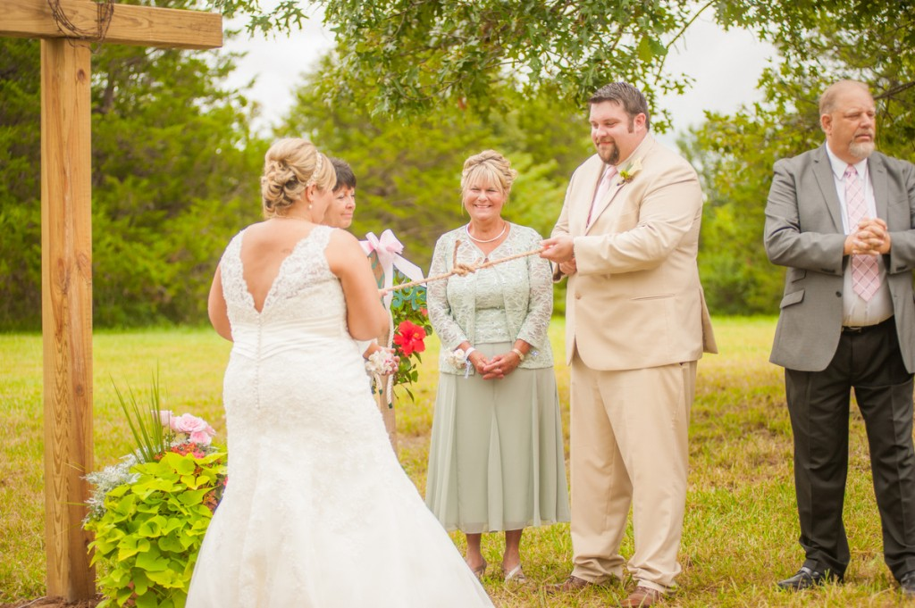 """Our wedding was held on Cedar Brook Farms, our fifth generation family farm in Fulton, Missouri. We got married at 10:30 AM the morning of August 9, 2014 in the Lone Oak Chapel, a well manicured pasture surrounded by cedar trees and flanked by one double-trunked oak tree in the center. Our ceremony was unique and ours--we had all FOUR of our grandmothers as flower girls, and our nephews paraded down the aisle with signs, our dog, and an antique wagon. In lieu of the tradtional unity candle, we actually """"tied the knot"""" using jute rope. Our musicians were all close friends who played poular music on their instruments (bassoon, cello, guitar, violin, and keyboard). Notably, I walked down the aisle to Bruno Mars' """"The Way You Are"""" as arranged by my best friend Taylor Smith. Our favors were snack bag programs filled with some of our favorite treats. Following the ceremony, our 300 guests rode horse drawn wagons across the pasture to the recently restored Old Farmhouse, where my great grandmother lived for many years. Guests enjoyed passed hors devours and a brunch buffet, including made-to-order omelettes, pancakes/waffles, prime rib, and bottomless mimosas and sangria (out of mason jars, of course). Instead of the dollar dance, guests contributed to our honeymoon fund by putting dollars in the cigar box of the person (bride or groom) they most wanted to see in a dunk tank. Near the end of the reception, we counted the dollars, and I got to dunk my husband. Guests lined up to take their turns as well. We ended the day with Kenny Chesney's """"It's That Kind of Day"""" and exited into the farmhouse. Our wedding was farm vintage chic. Our centerpieces and decorations were entirely comprised of antiques collected by close family and friends and fresh flowers grown and arranged by the local florist, a family friend, and my mom. My family did all the preparations--making and painting rustic signs, making hundreds of yards of bunting, and building the ceremony altar, the cross, and """