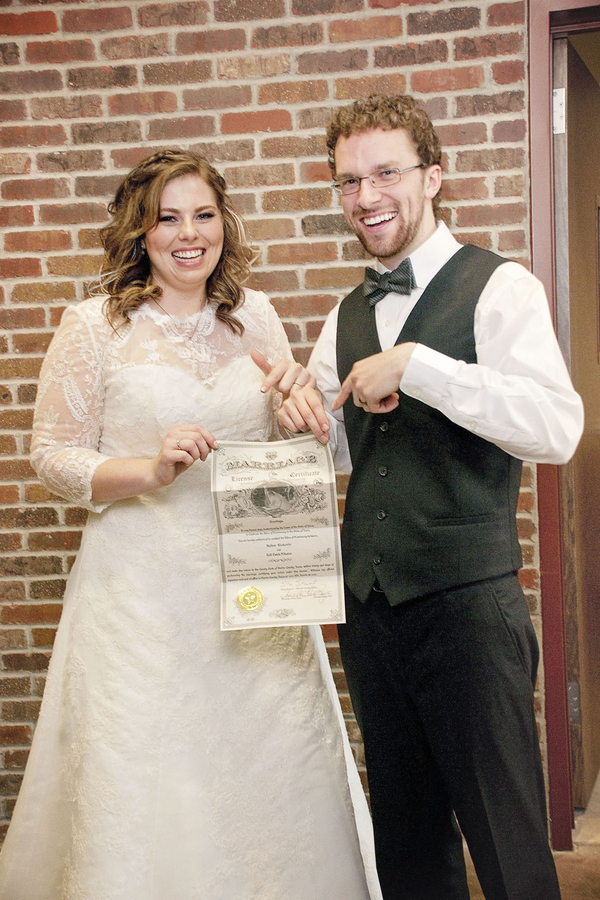Gorgeous plus size bride and her dapper groom with their marriage license
