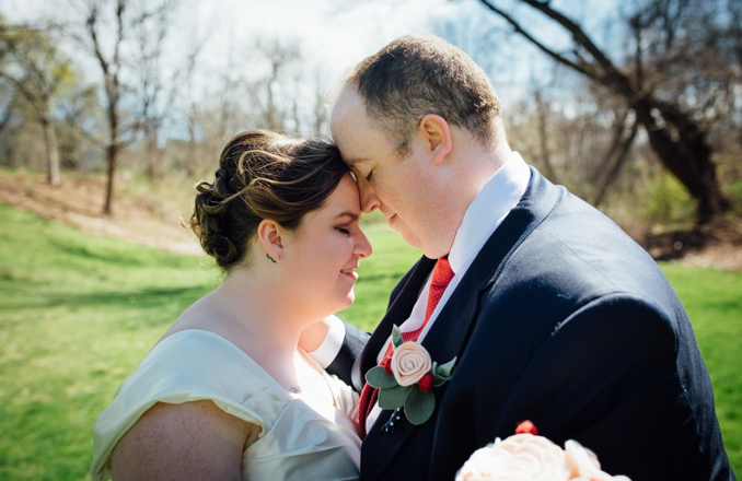 plus size bride and groom in a field