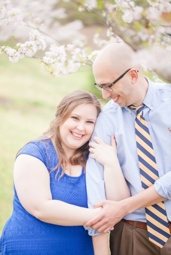 plus size bride to be and groom by a tree