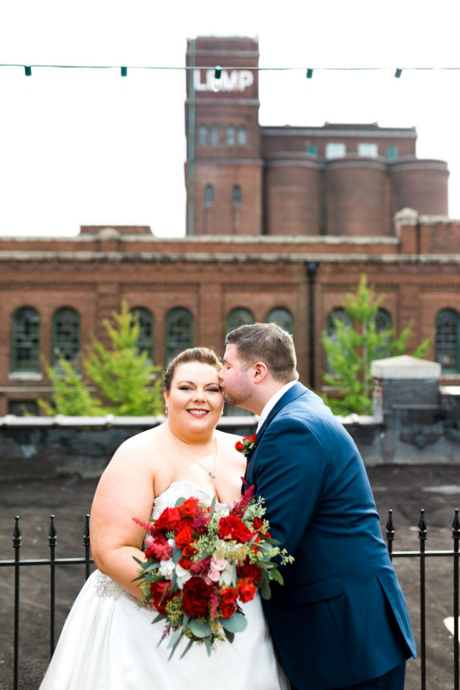 plus size bride wearing A-line dress and groom wearing navy suit